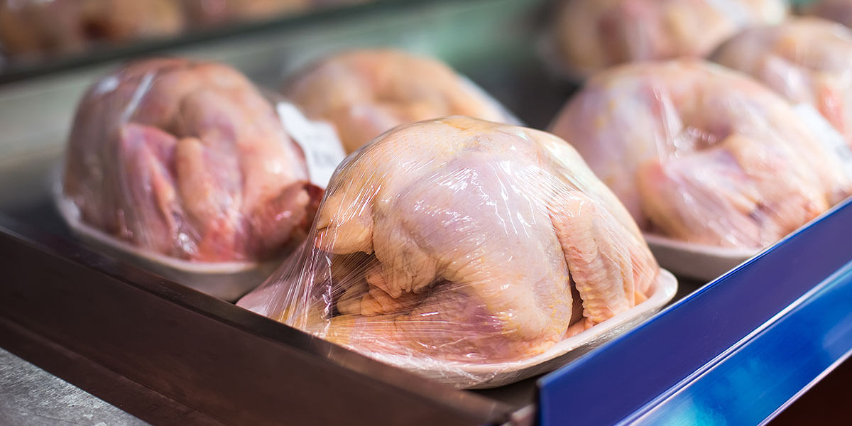 Multiple whole chicken carcasses wrapped in plastic on a table.